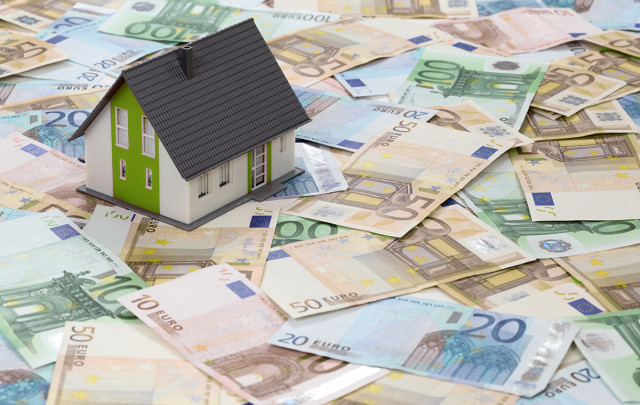 Dinero en Euros y sobre ellos una maqueta de casa