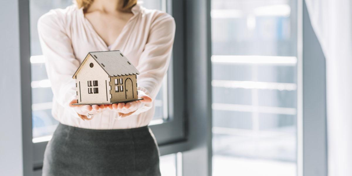 Mujer sosteniendo en sus manos una casa