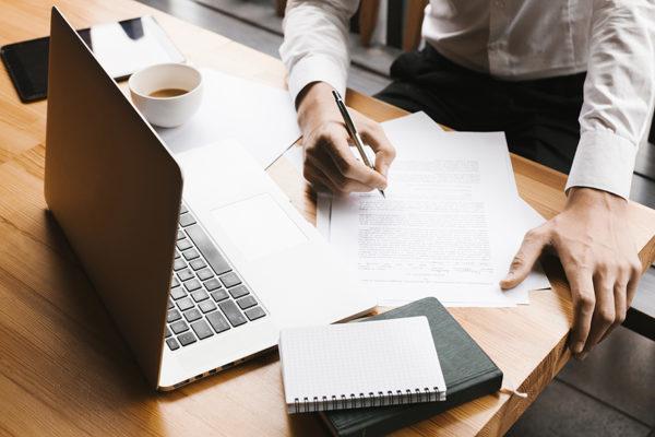 Asesor de Gestcredit en su oficina con la documentación de FiAE y la FEIN que se requiere para una hipoteca